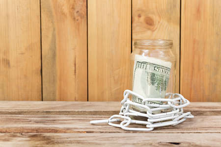 Money in a glass jar and chain on a wooden table photo