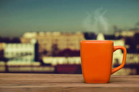 sill: Steaming coffee on the window background. Cup on a wooden window sill against the evening city Stock Photo