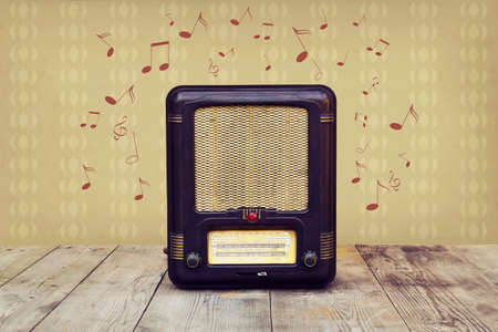 Retro radio on a wooden floor over vintage wallpaper photo