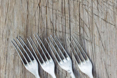alluminum: Background with  retro forks on wooden table. Old alluminum forks