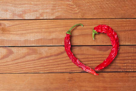 Photo of red heart shape chili pepper on wooden background. Dry spice photo