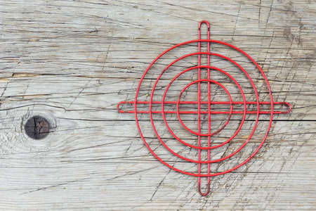 Red metallic crosshair on an old wooden surface photo
