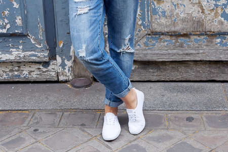 worn jeans: Young girl stands in the sneakers crosslegged. Close-up shoes. Trendy white sneakers and worn jeans boyfriend Stock Photo
