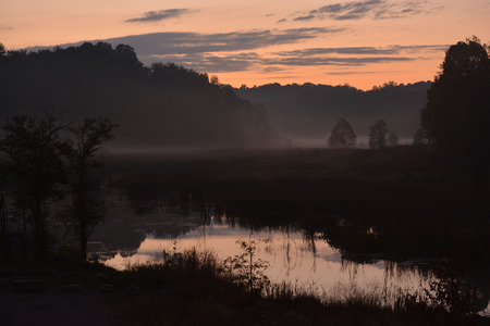 Fog settling by the lake at sunset