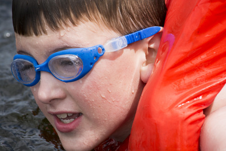 boy swimming  in lake with life vest
