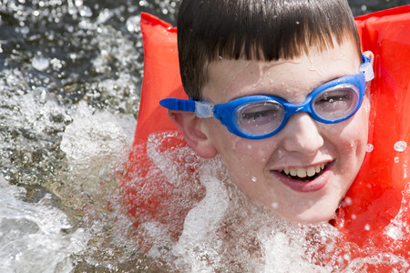 boy swimming and splashing in lake with life vest