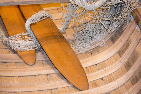 paddles in wooden canoe with net