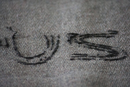 US embroidered on old wool blanket