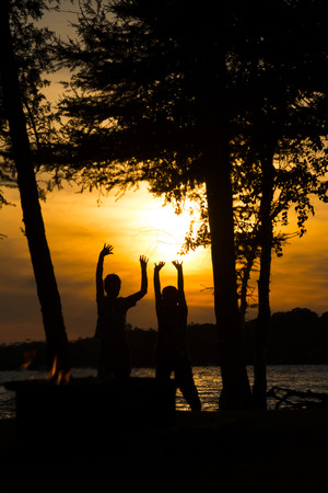 silhouette of boys holding up the sun Stock Photo