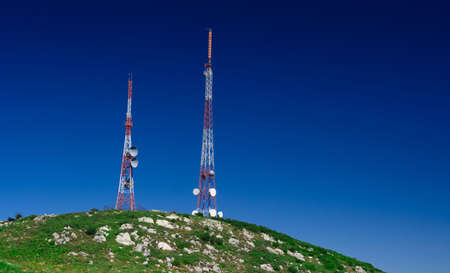 Telecommunication tower on the green field with blue sky Banco de Imagens