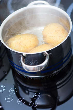 boiling pot: potato boiling in water Stock Photo