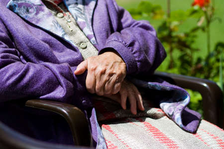 incapacitated: Elderly Woman in sunlight siting Stock Photo
