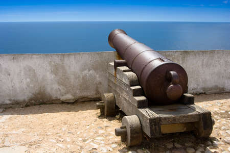 cannon: Old fashioned sea cannon aimed at sea in Portugal