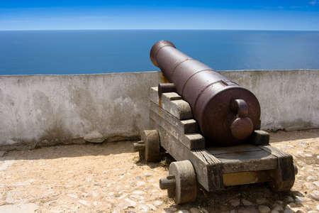 Old fashioned sea cannon aimed at sea in Portugal
