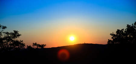 siluet: wounderful sunset with sun and siluet of trees and mountains