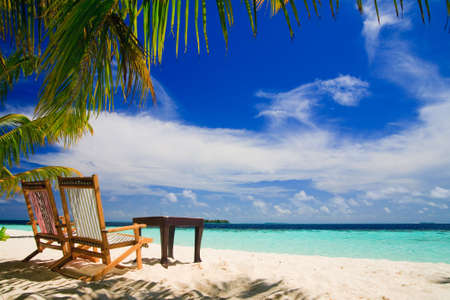 beach scene: Relaxing on tropical paradise with white sand at Maldives and green palms with blue sky