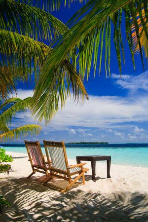 strandstoel: Ontspannen op het tropische paradijs met wit zand op de Malediven en groene palm bomen met blauwe hemel  Stockfoto