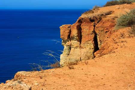 cap at Algarve, rocks and blue sea photo