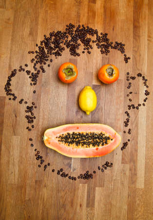 face made of fruits on wooden background photo