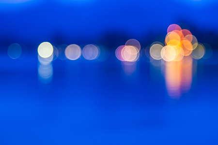 боке: Размытыми огнями отражающие воду Фото со стока