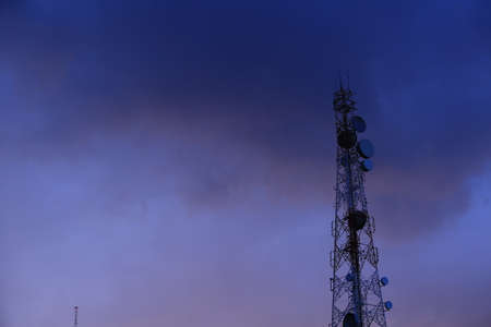 Telecommunication tower Antenna and satellite dish at sunset sky background.
