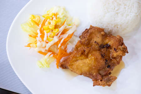 Fried chicken with rice in a white dish with vegetables, carrots, corn and lettuce. Foto de archivo