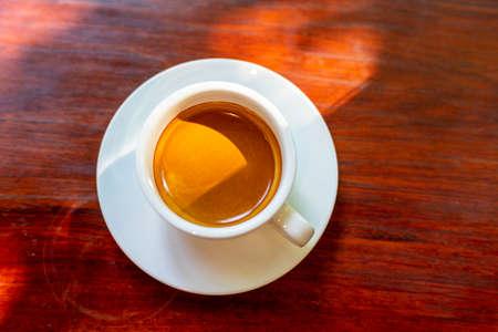 Espressokaffee in Holztablett, schwarzer Hintergrund.