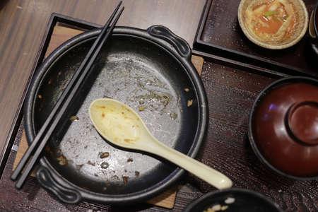 A dirty black plate, spoon and chopsticks. Stockfoto