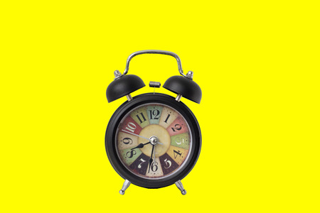 black vintage alarm clock on yellow color background