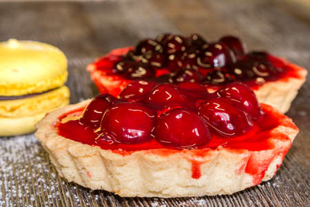 dulcet: Confectionery basket with cherries, macaroon and cake with cream on a dark wooden background Stock Photo