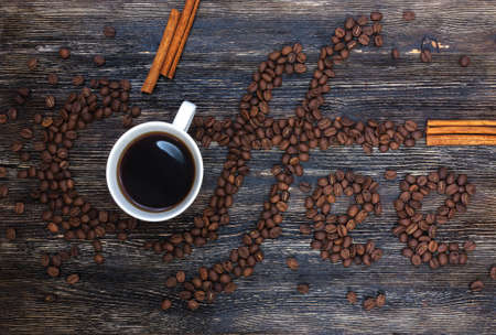 Beautiful title Coffee written of coffee beans on wooden table