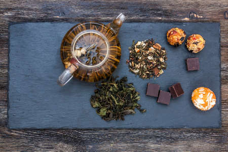 Green tea with cake, dried fruits and chocolate