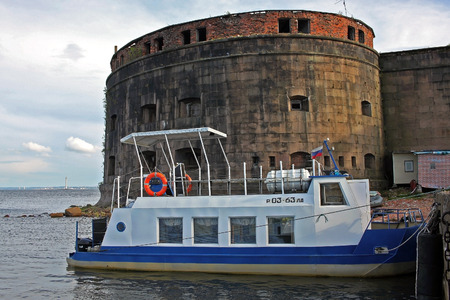 Kronstadt, Russia - 10 July 2016: Tour boat moored at the Fort Alexander I, or Plague Fort.  Fort built in the years 1836-1845. In 1899–1917 the fort housed a research laboratory on plague and other bacterial diseases. Editorial
