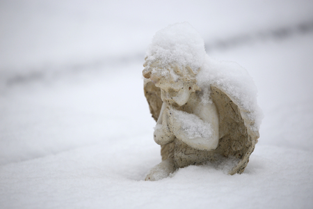 statue of small angel in snow at municipal cemetery in Amsterdam, The Netherlands Imagens