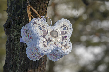 close-up view of stone butterfly with mosaics hanging on tree at municipal cemetery in Amsterdam, The Netherlands
