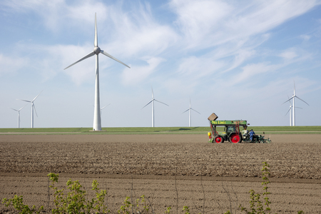 View of combine harvester on field with windmills