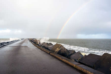 Ijmuiden pier with rainbow in the Netherlands 스톡 콘텐츠