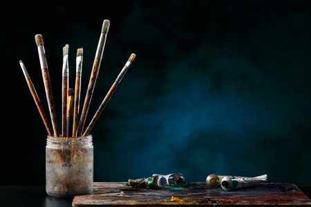 Cepillos de pintura con una paleta en un fondo coloreado.