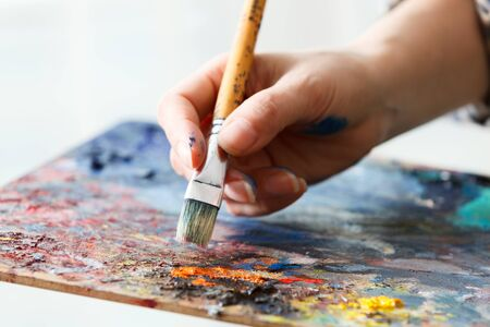 Artist paints a picture of oil paint brush in hand with palette close up. Stock Photo