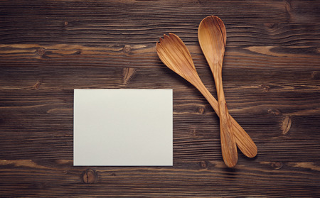 page background: Close up wooden spoons, and blank paper on wooden board. Top view.