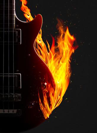 enveloped: Electronic bass guitar enveloped flames on a black background.