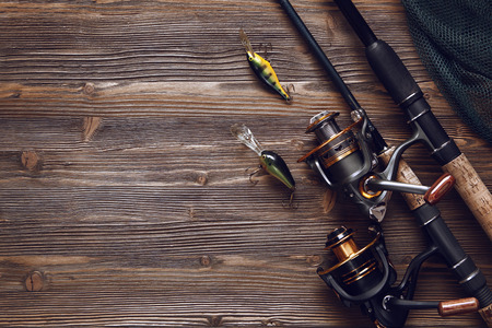 darken: Fishing tackle - fishing spinning, hooks and lures on darken wooden background.Top view.