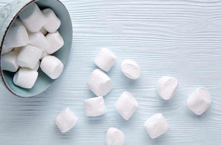 marshmellow: White marshmallow in a cup on a light wooden background. Stock Photo