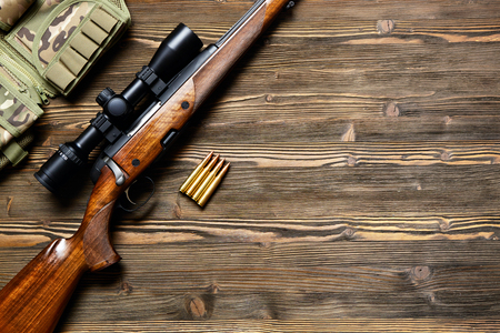 Hunting rifle and ammunition on a dark wooden background.Top view.