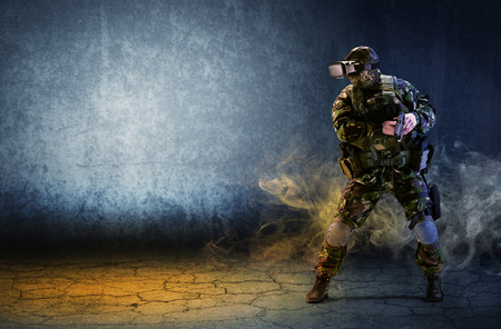 A soldier with virtual reality glasses is holding a pistol in his hands. The concept of a virtual hologram. Simulation Games.