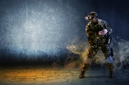 Un soldat avec des lunettes de réalité virtuelle tient un pistolet dans ses mains. Le concept d'un hologramme virtuel. Jeux de simulation.