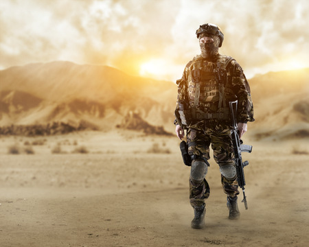 A soldier of special forces walks through the desert.