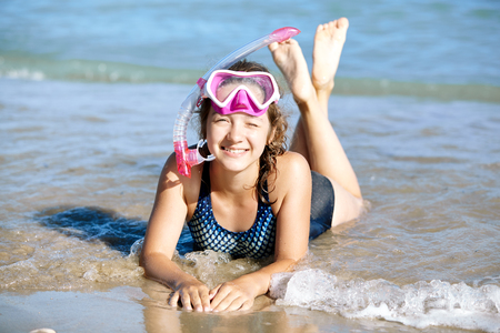 Happy young girl lies on the beach in fins and masks for scuba diving. Healthy lifestyle.
