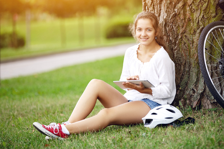 A beautiful young girl sits in a park on the grass and uses a tablet. Technology internet modern lifestyle concept.