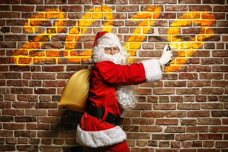Christmas concept. Astonished Santa Claus writing on a brick wall painted. Stock Photo